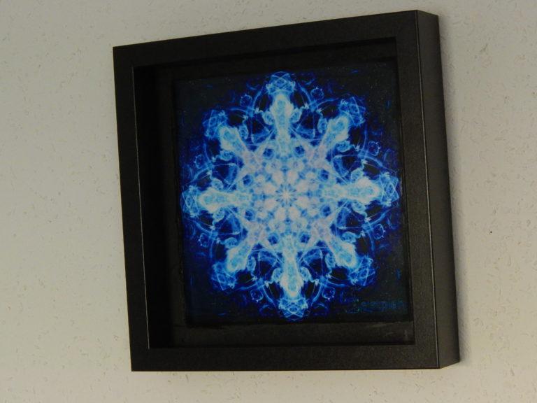 Blau leuchtendes psychodelisches Mandala in einem Objektrahmen. Kräftige blau leuchtende Farben