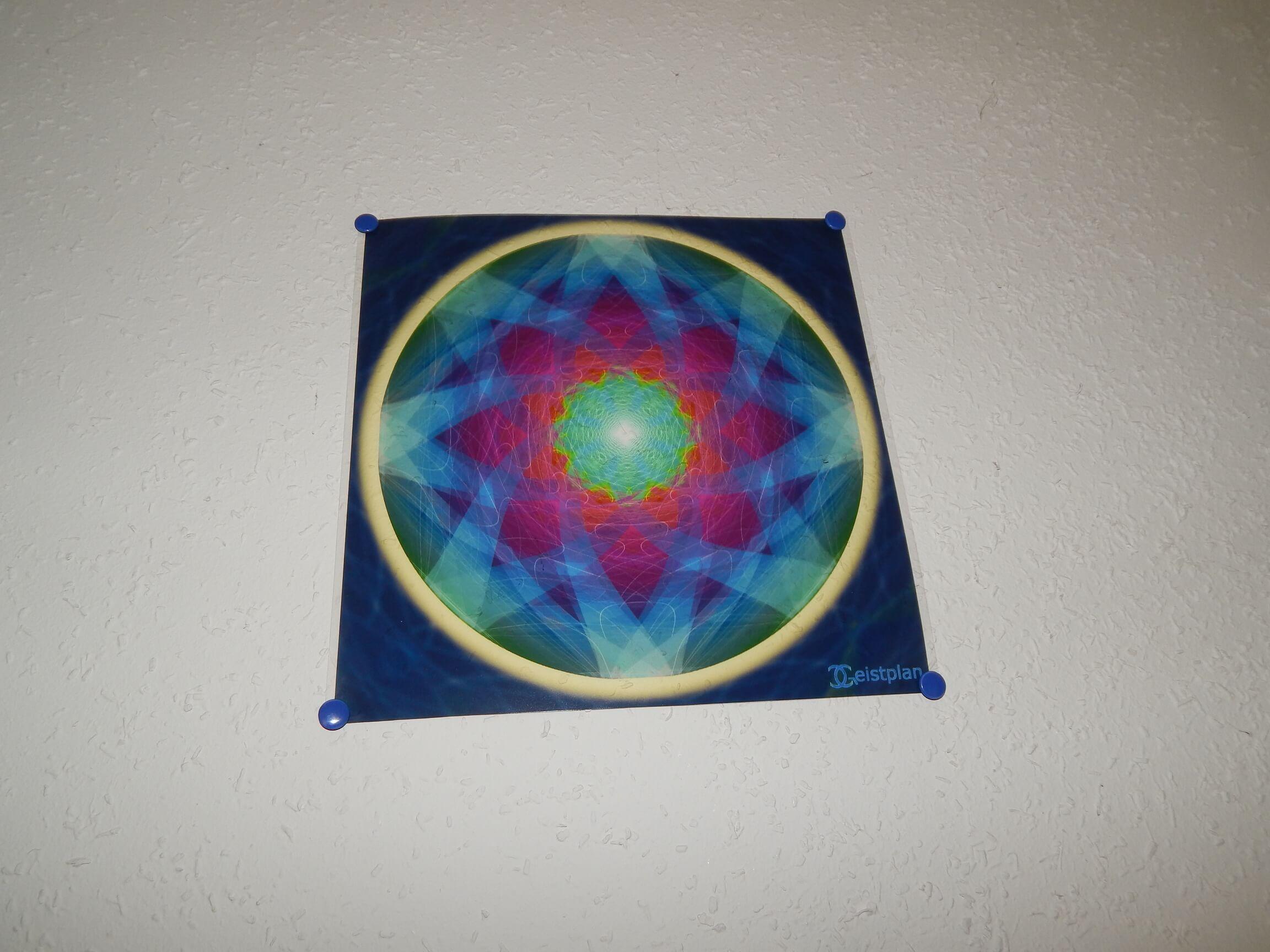 Bild von einer Folie an der Wand, welche ein Mandala abbildet und die Farben leuchten