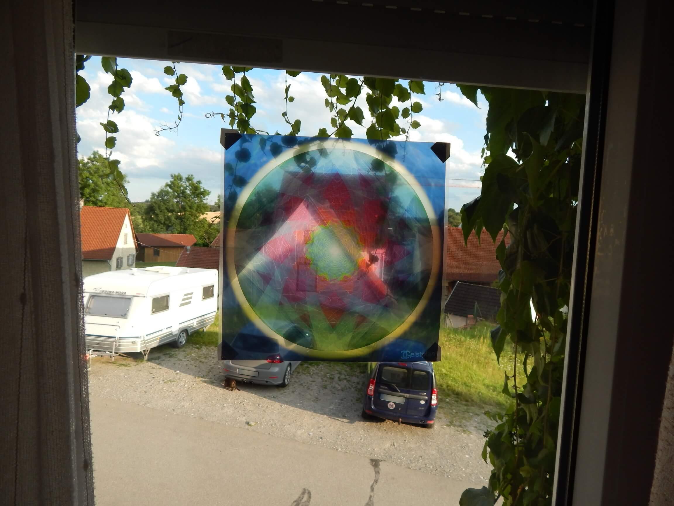 Foto von einem Fensterbild welches ein Mandala abbildet. Farben des Mandalas Rot, Blau, Gruen und Gelb