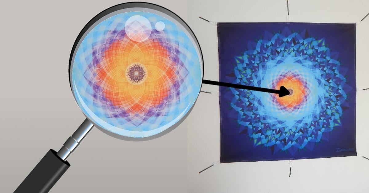 Foto von einem Tuch mit Karabinern, dass ein Mandala abildet. Daneben eine virtuelle Lupe die das Zentrum des Bildesvergrößert und die filigranen Linien des blau, violett und orangeroten Mandala zeigt.