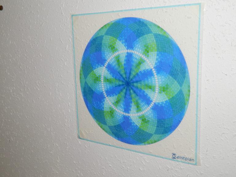 Bild von eine Folier die an einer weißen Wand hängt und ein Mandala (eingefärbter Torus) abildet.