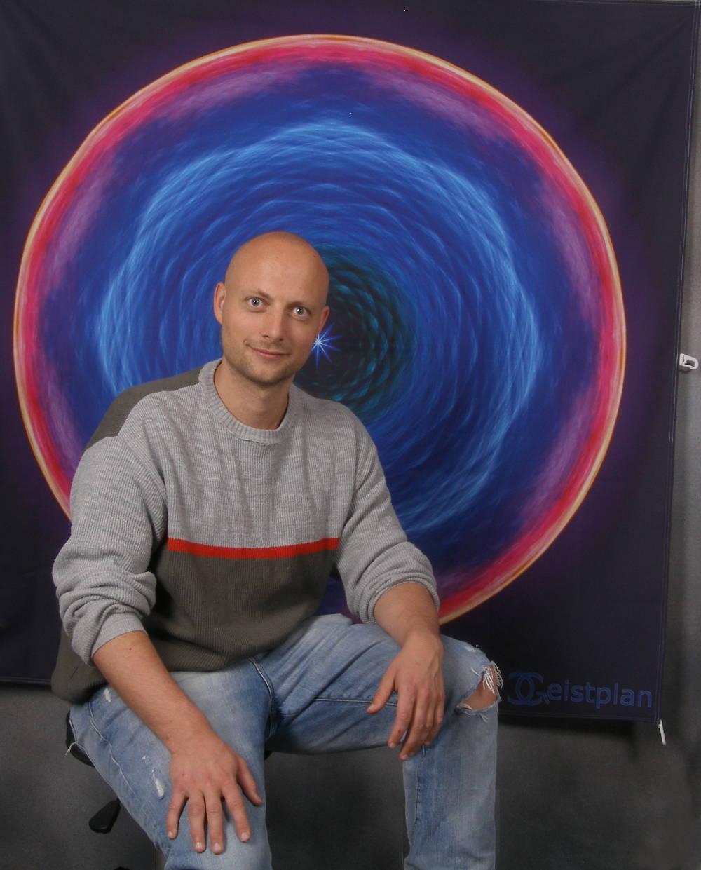 Bild zeigt eine Person sitzend vor einem wirklich großen Mandalatuch
