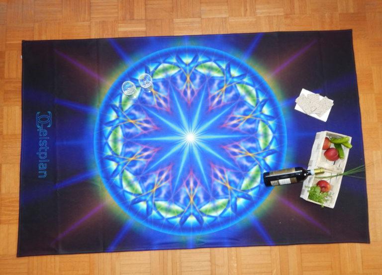 Mandala psychodelisch mit Strahlen und dark background auf einer Fleecedecke. Die Farbentiefe leuchtet einen an.