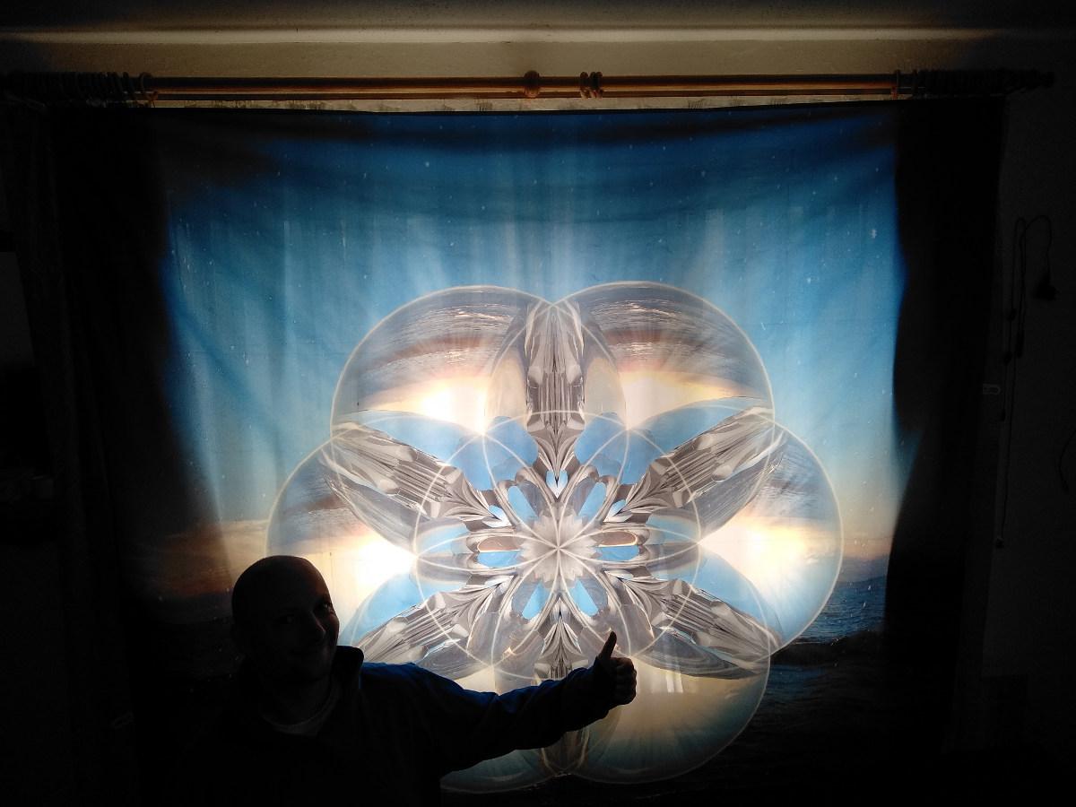 Wandbehang als Tuch als Vorhang, welches hinterleuchtet wird von der Sonne. Blaue Muster