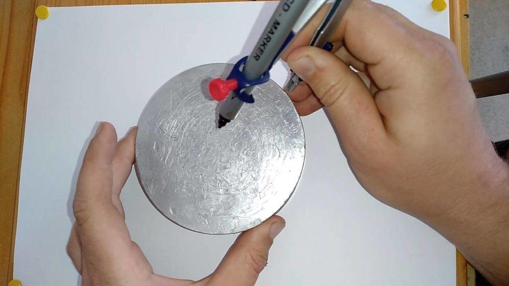 Bild von einer Aluscheibe, in der seitlich mit einem Zirkel eingestochen wird.