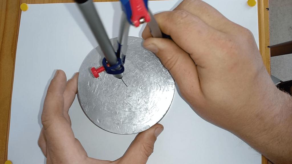Bild von einer Aluscheibe,welche in der Mitte mit einem Zirkel markiert wird.