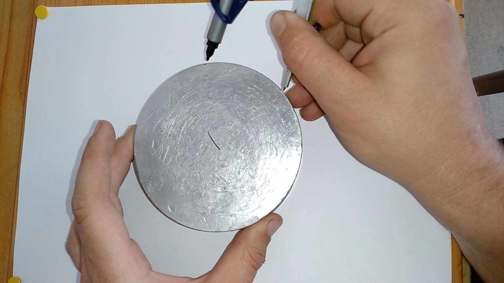 Bild von einer Aluscheibe, welche mit dem Zirkel zwei Markierungen bekommen hat.