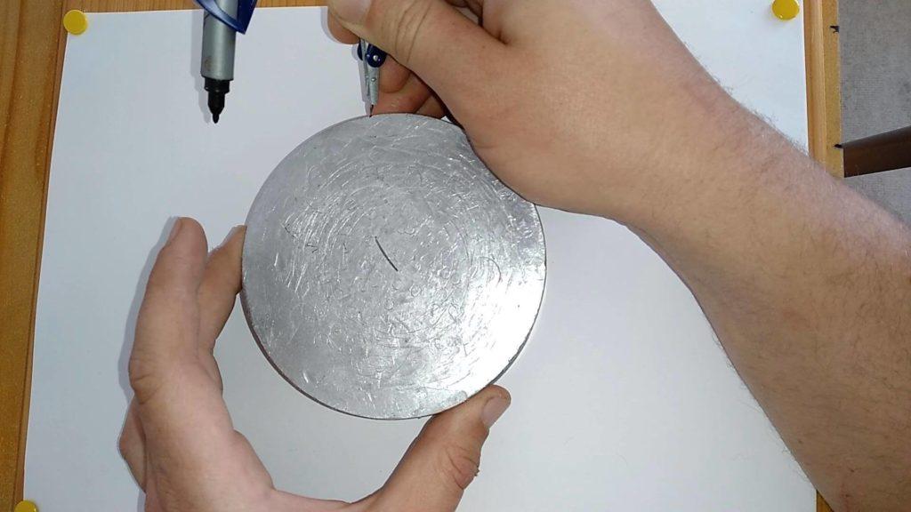 Bild von einer Aluscheibe, in diese wird seitlich in die Markierung mit dem Zirkel eingestochen. Anleitung: einen Kreismittelpunkt finden