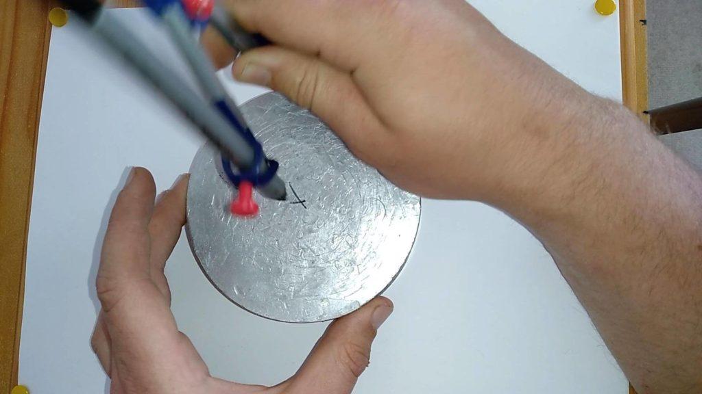 Bild von einer Aluscheibe, welche mit dem Zirkel drei Markierungen bekommen hat. Anleitung: einen Kreismittelpunkt finden