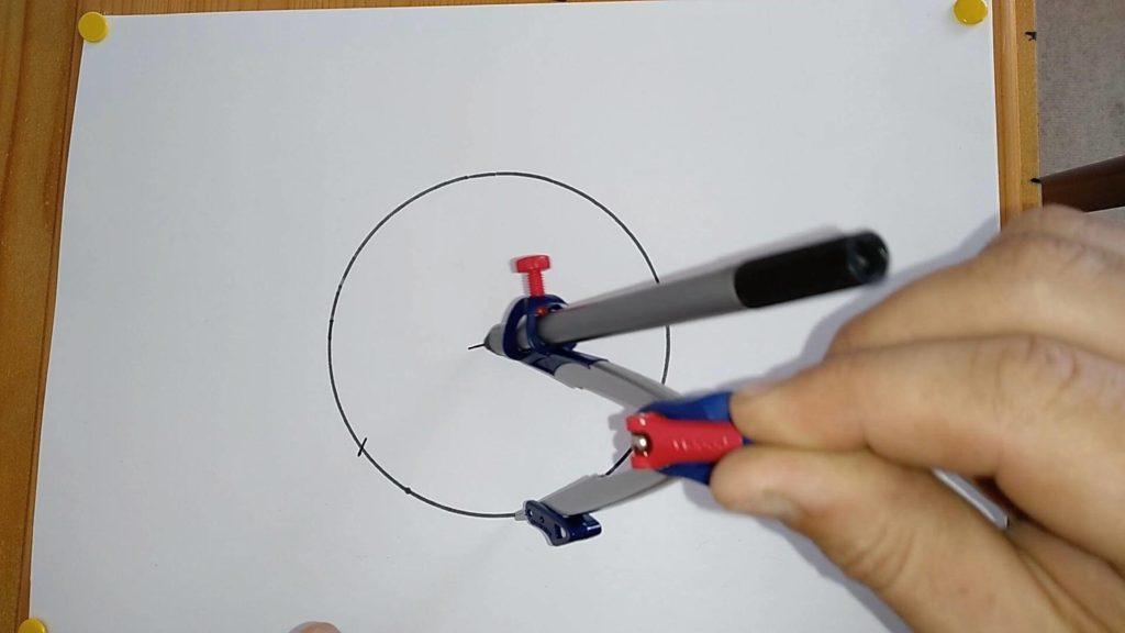 Bild von einem gezeichneten Kreis, in welchen mit einem Zirkel der Mittelpunkt eingezeichnet wird. Anleitung: einen Kreismittelpunkt finden