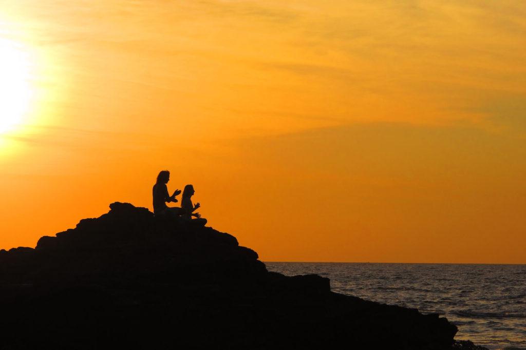 Bild von einem Pärchen, das auf einem Felsen am Meer meditiert, Meditieren lernen