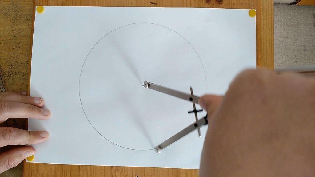 Bild von einem Kreis, welcher mit einem Zirkel gezeichnet wird