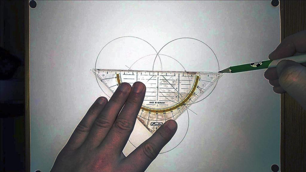 Bild von einem Geodreieck und BleIstift, mit dem eine Gerade durch Kreise gezogen wird.