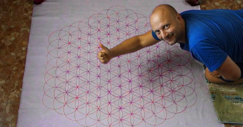 Bild von einer großen Folie, mit Konrad der daruf kniet. Auf der Folie ist wunderschön die Blume des Lebens gezeichnet.Anleitung Blume des Lebens groß zeichnen und malen