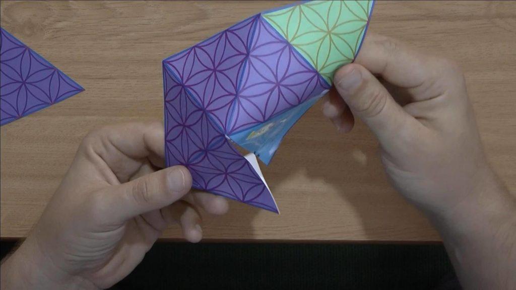 Bild von einer Schablone mit Blume des Lebens Muster, die zur einer Viereckspyramide gefaltet wird.