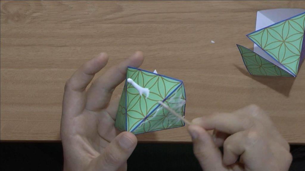 Bild von einer Papierpyramide, welche mit Klebstoff beschmiert wird. Anleitung: eine Pyramide oder einen Oktaeder mit einer Schablone basteln