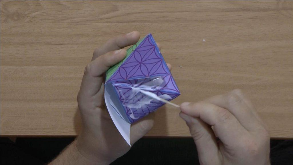Bild von einer Papierpyramide, welche mit Klebstoff beschmiert wird